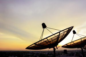Satellite dishes on twilight sky background